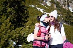 Deux ont équipé des femmes de randonneur riant dans une haute montagne Photographie stock