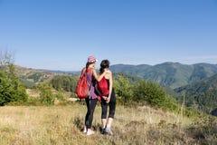 Deux ont équipé des femmes trimardant dans une haute montagne d'automne Photographie stock