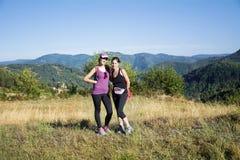 Deux ont équipé des femmes trimardant dans une haute montagne d'automne Image stock