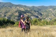 Deux ont équipé des femmes trimardant dans une haute montagne d'automne Photographie stock libre de droits