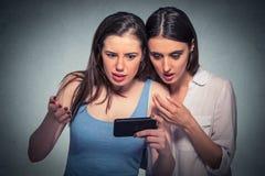 Deux ont étonné des filles regardant le téléphone portable discutant les dernières actualités de bavardage Photos libres de droits