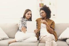 Deux ont choqué les amis féminins à l'aide du comprimé Photographie stock libre de droits
