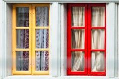 Deux ont coloré des fenêtres avec des rideaux sur le mur en pierre Images stock