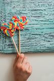 Deux ont coloré la sucrerie rayée d'arc-en-ciel sur un bâton sous forme de coeur sur un fond en bois de vieux vintage bleu Le con Images libres de droits