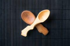 Deux ont croisé les cuillères en bois faites main vides du bois différent et images stock