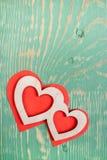 Deux ont découpé les coeurs en bois se trouvent sur les coeurs de papier rouges sur la table en bois texturisée verte Vue supérie Photographie stock libre de droits