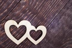 Deux ont découpé les coeurs en bois se trouvent sur les planches texturisées diagonales foncées avec l'espace de copie Photo libre de droits