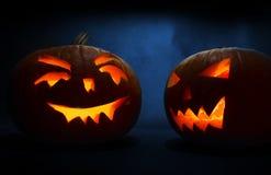 Deux ont découpé des visages des potirons rougeoyant Halloween sur le fond bleu Image libre de droits