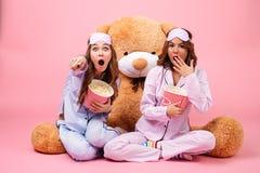 Deux ont effrayé de jolies filles habillées dans des pyjamas dirigeant le doigt Photo libre de droits