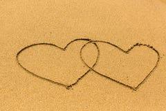 Deux ont empêtré des coeurs dessinés sur une plage sablonneuse Amour Image stock