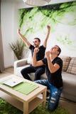 Deux ont excité des amis ou des compagnons de chambre regardant la TV sur la ligne se reposant sur un divan dans le salon à la ma Photographie stock libre de droits