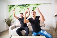 Deux ont excité des amis ou des compagnons de chambre regardant la TV sur la ligne se reposant sur un divan dans le salon à la ma Images libres de droits