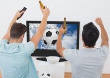 Deux ont excité des hommes encourageant avec la bouteille à bière tout en observant la manifestation sportive à la TV Image libre de droits