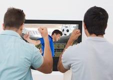 Deux ont excité des hommes encourageant tout en observant le match de football à la TV Photos libres de droits