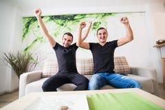 Deux ont excité des hommes s'asseyant sur le divan et le football préféré de observation d'équipe avec le but Photographie stock libre de droits