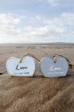 Deux ont inscrit les coeurs en bois d'amour dans le sable Photo libre de droits