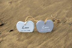 Deux ont inscrit les coeurs en bois d'amour dans les sables mouvants Photographie stock libre de droits