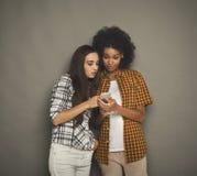 Deux ont intéressé les amis féminins à l'aide du smartphone Photo libre de droits