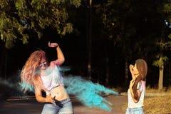 Deux ont satisfait des amis de jeune femme ayant l'amusement avec éclater Holi p Images stock