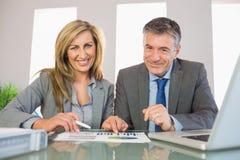 Deux ont satisfait des gens d'affaires souriant à l'appareil-photo analysant un graphi Photo libre de droits