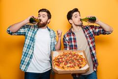 Deux ont satisfait des hommes dans des chemises buvant de la bière tout en tenant la pizza Image stock