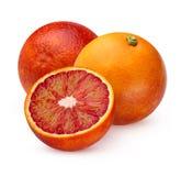 Deux oranges et moitiés rouges ensanglantées entières d'isolement sur le backgrou blanc Photos libres de droits
