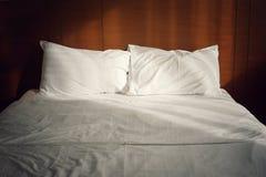 Deux oreillers et couvertures sur le lit dans le vintage modifient la tonalité avec l'éclairage naturel Photographie stock
