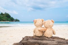 Deux ours de nounours se reposant sur le bois de construction avec la vue de mer Amour et Re Image libre de droits