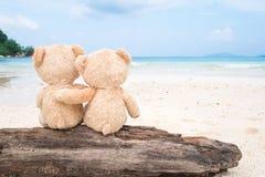 Deux ours de nounours se reposant sur le bois de construction avec la vue de mer Amour et Re Photo stock