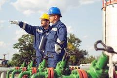 Deux ouvriers discussion et pointage pour l'inspection image stock