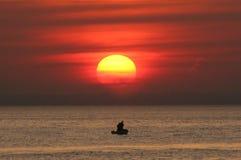 Deux pêcheurs dans le bateau au coucher du soleil Photo stock