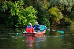 Deux pêcheurs dans un bateau avec les cannes à pêche pêchant des poissons Photos libres de droits