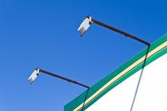 Deux pôles de lumières d'endroit sur le panneau-réclame Photos stock