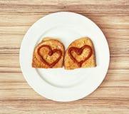 Deux pains frits dans l'oeuf avec des coeurs de ketchup, valentine FO Photographie stock libre de droits