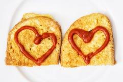 Deux pains frits dans l'oeuf avec des coeurs de ketchup, valentine FO Photo stock