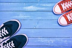 Deux paires d'espadrilles sportives, d'espadrilles bleues du ` s d'hommes et de wome rouge Photographie stock
