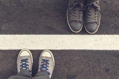 Deux paires d'espadrilles sur une route d'asphapt Photo stock