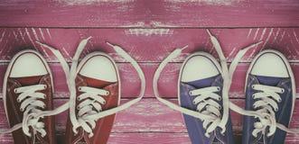 Deux paires d'espadrilles usées sur une vieille surface en bois rose Photographie stock libre de droits