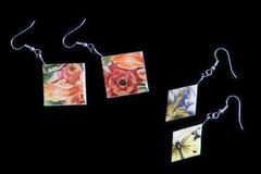 Deux paires de boucles d'oreille en bois avec une impression florale sur un fond foncé photographie stock libre de droits