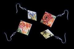 Deux paires de boucles d'oreille en bois avec une impression florale sur un fond foncé photo libre de droits
