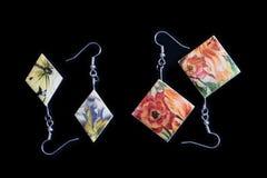 Deux paires de boucles d'oreille en bois avec une impression florale sur un fond foncé image libre de droits