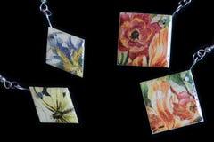 Deux paires de boucles d'oreille en bois avec une impression florale sur un fond foncé photos stock