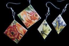 Deux paires de boucles d'oreille en bois avec une impression florale sur un fond foncé images libres de droits