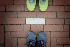 Deux paires de chaussures de course se tenant derrière chaque autres sur le passage couvert de brique rouge avec la ligne blanche image libre de droits