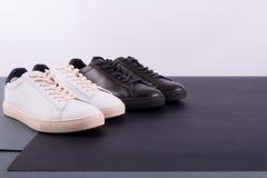 Deux paires de chaussures d'espadrilles sur le fond noir Chaussure noire et blanche Photographie stock libre de droits