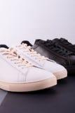 Deux paires de chaussures d'espadrilles sur le fond noir Chaussure noire et blanche Photo stock
