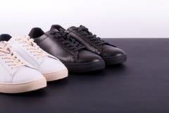 Deux paires de chaussures d'espadrilles sur le fond noir Chaussure noire et blanche Photos stock