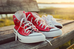 Deux paires de chaussures de sports sur un banc au coucher du soleil Photo libre de droits
