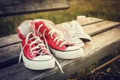 Deux paires de chaussures de sports sur un banc au coucher du soleil Photos stock