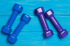 Deux paires de gantelae sur les conseils, les haltères de bleu et de lilas, le sport de concept et la forme physique bleus Photographie stock libre de droits